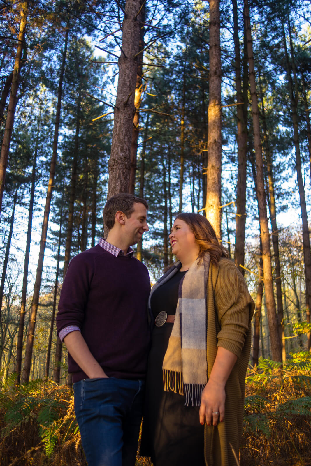 Young couple looking at each other amid tall thin fir trees
