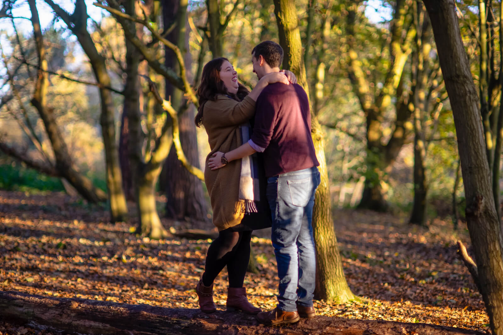Engaged couple laughing and embracing in the woods in the evening sun