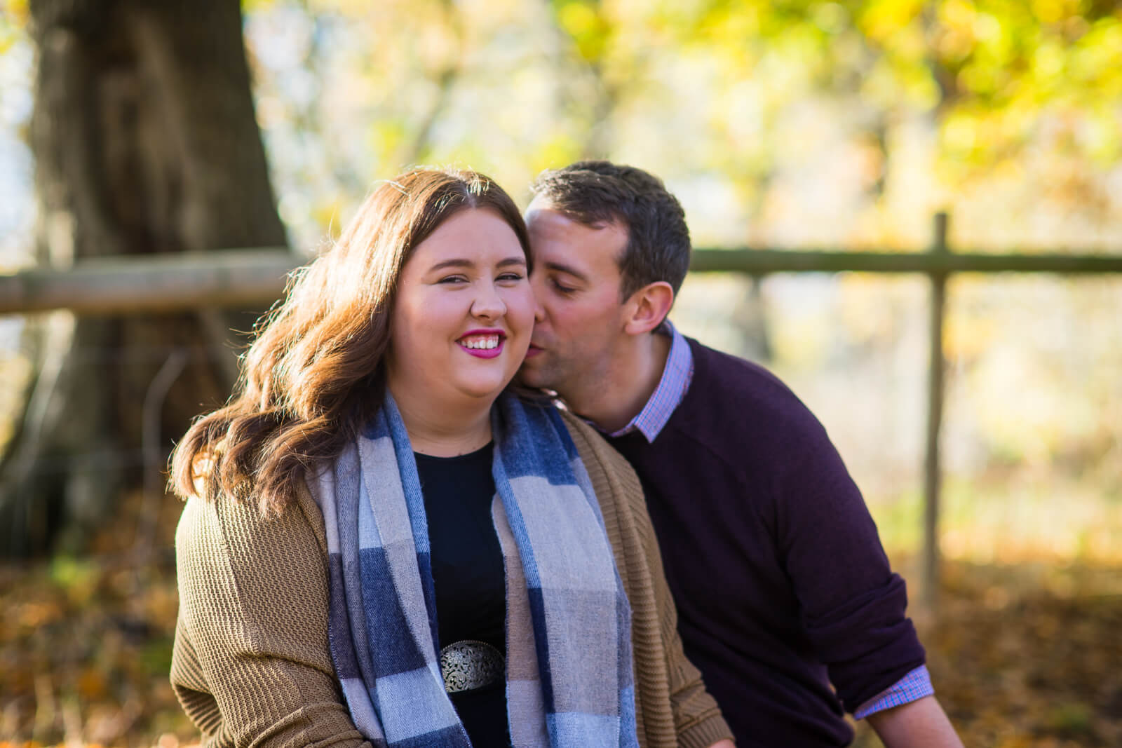 Young man kisssing his fiance on the cheek in autumn sunshine