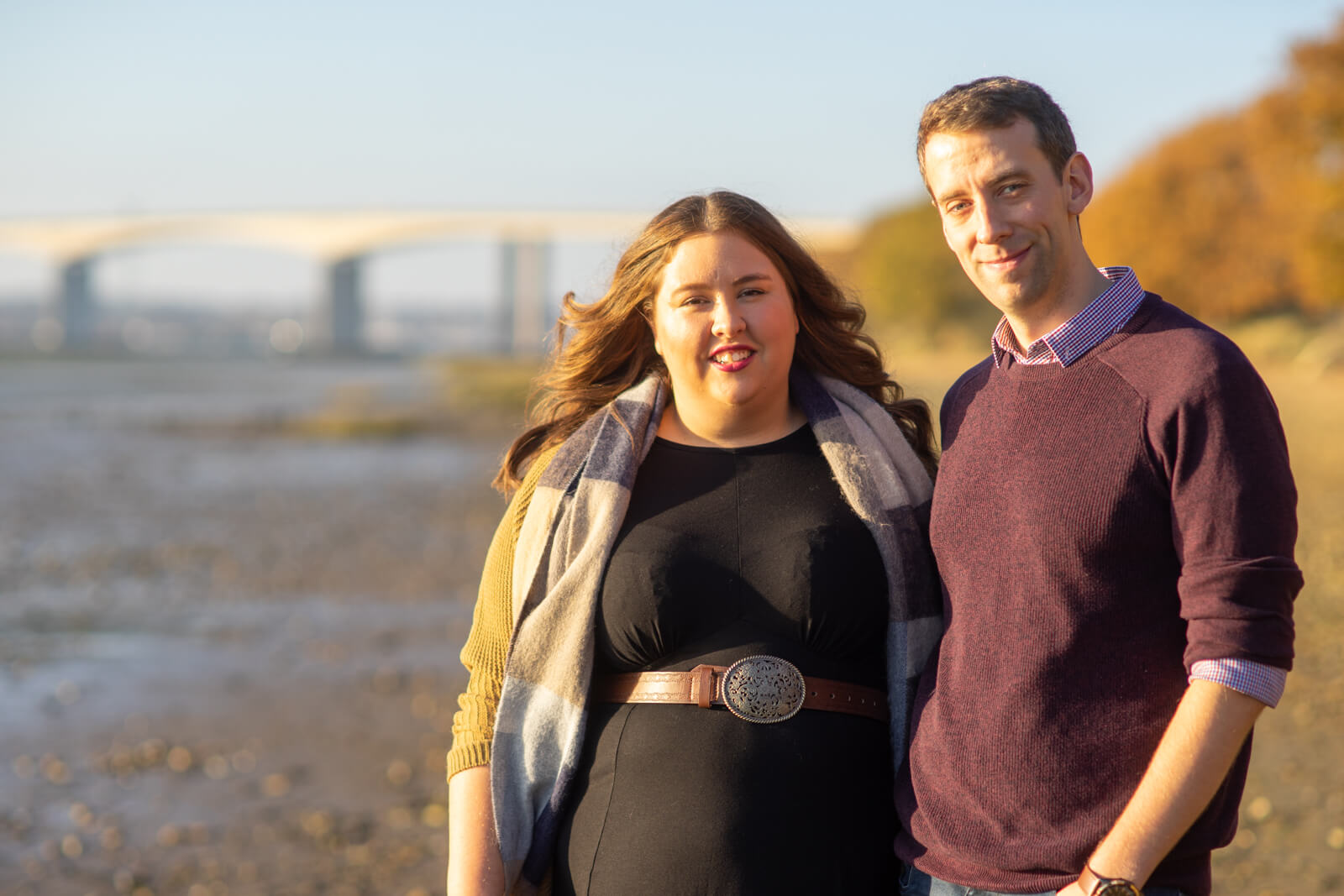Engagement photo of young couple on the beach beside the river orwell wit the bridge in the background