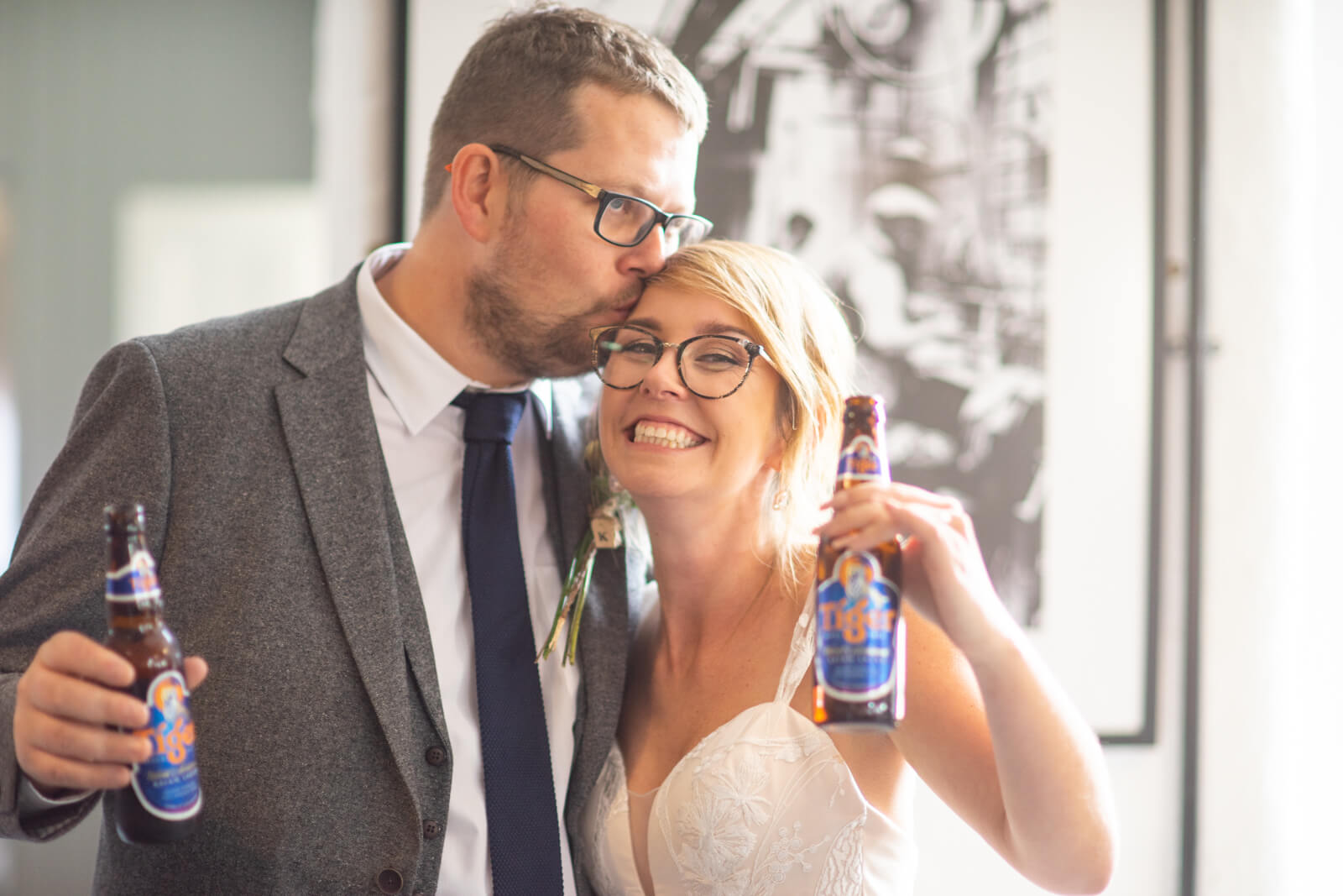 Groom kisses bride on the head as they both hold up their bottles of beer